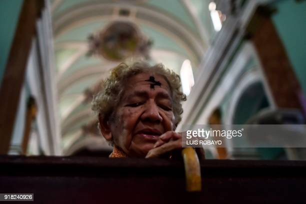 Catholic faithful with her forehead marked with ash prays during the celebration of Ash Wednesday in Cali Colombia on February 14 2018 Ash Wednesday...