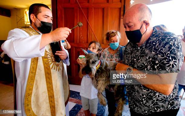 Catholic faithfull wearing face masks bring their pets to be blessed at the Church of Saint Francis of Assisi, patron saint of animals, whose feast...