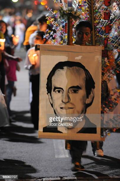 Catholic faithfuls carries a portrait of Father Ignacio Ellacuria during a procession to commemorate the XX anniversary of his murder and five...