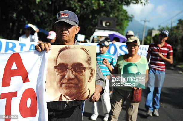 Catholic faithfuls participate in a march to celebrate the 92nd birthday of the late archbishop of San Salvador Oscar Arnulfo Romero carrying signs...