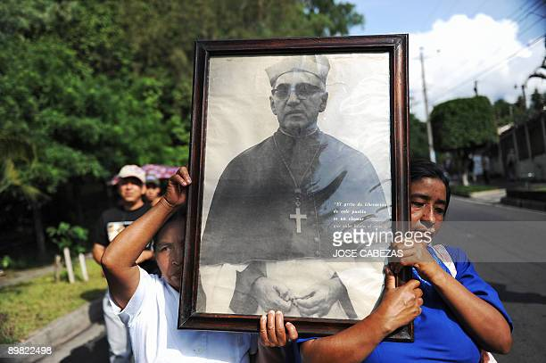 Catholic faithfuls participate in a march to celebrate the 92nd birthday of the late archbishop of San Salvador Oscar Arnulfo Romero carrying a...