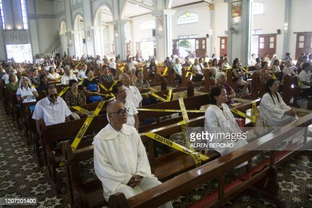 Catholic faithfuls sit on chairs with yellow line tapes to separate church goers from sitting close to each other as part of social distancing at a...