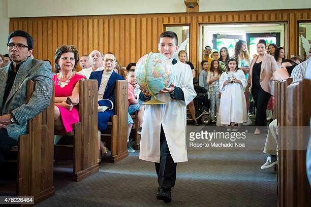 Catholic First Communion Ceremony: Adolescent boy carrying globe down isle dressed in white robe in a church while the congregation looks on.