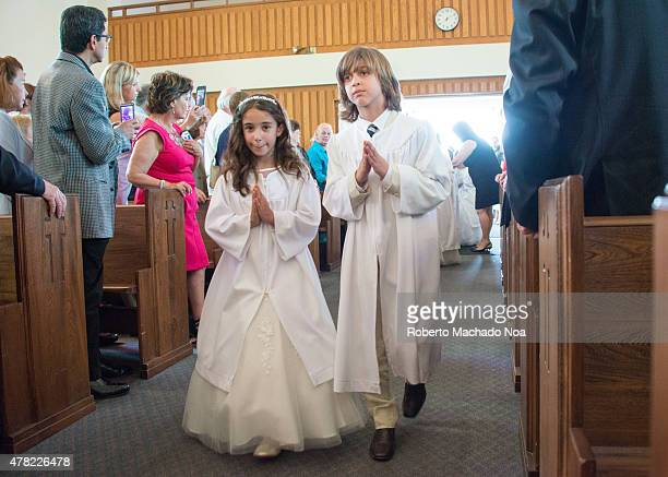 Catholic First Communion Ceremony Little Catholic girl and boy dressed in white with their hands in prayer position walking down the isle to receive...