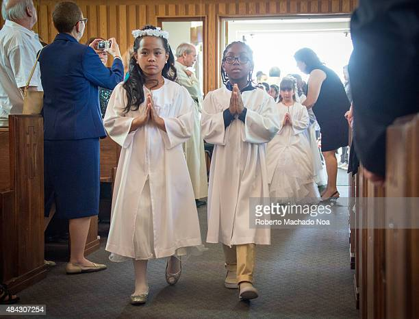 Catholic First Communion Children walk the aisle at first holy communion ceremony All the young girls are all dressed in white robes and dresses...