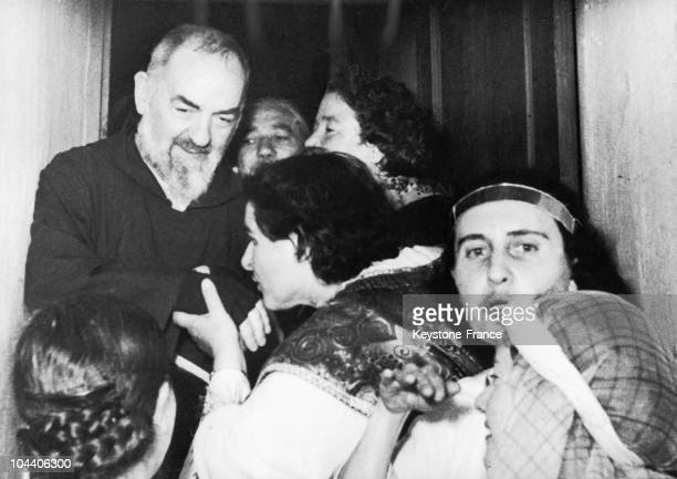 Catholic followers swarming around Father PIO a priest who bears the stigmata of Christ to kiss his hands clad in mittens in San Giovanni Rotondo...