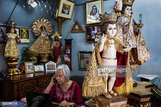 Catholic icon dealer Nene Bernales and embroidery staff at work in her shop in Manila Philippines January 25 2012 They are surrounded by Icons that...