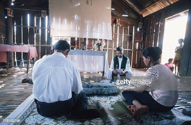 BOUSRA MONDOLKIRI CAMBODIA Catholic missionary Gerald Vogin prays as he delivers a blessing to a newly married couple in a wood and bamboo church in...