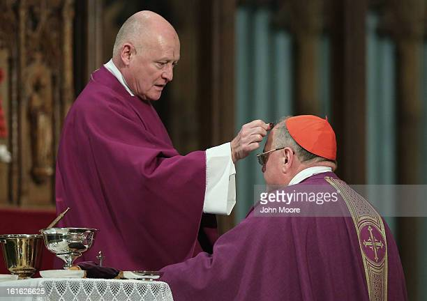 Catholic Monsignor Robert T. Ritchie rubs ashes onto the forehead of Cardinal Timothy Dolan, Archbishop of New York, while celebrating Ash Wednesday...