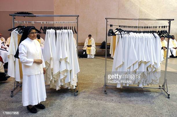 A Catholic nun and priests wait on August 15 2013 before a mass for the feast of the Assumption in the sanctuary of Our Lady in the French...