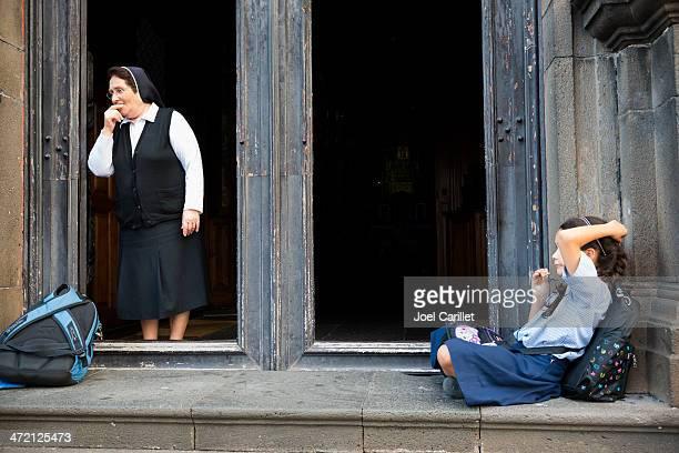 Catholic nun and school girl on church steps