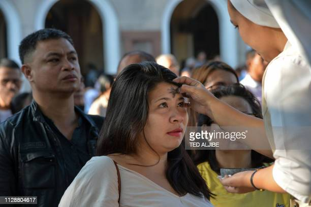 Catholic nun applies ash to a woman's forehead on 'Ash Wednesday' at a church in Manila on March 6, 2019. - The 40-day period of Lent begins on Ash...