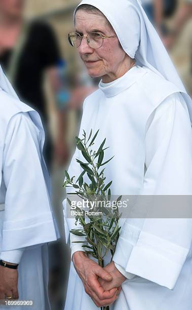 Catholic nun holding an olive branch in her hand as she makes her way downhill from the top of Mt. Of Olives. Palm Sunday procession in Jerusalem.
