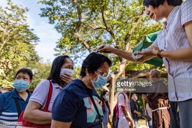 Catholic nun sprinkles ash on the head of a devotee during Ash Wednesday services at a church on February 26 2020 in Paranaque city Metro Manila...
