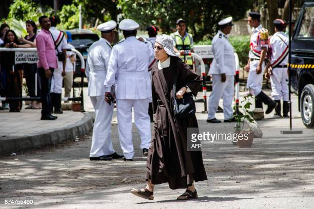 Catholic nun walks down a street past Egyptian security forces gathered around the Coptic Catholic College of Theology and Humanities in the southern...