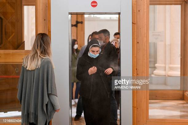 A Catholic nun wearing a face mask walks through a disinfection chamber during the first public mass at the Mother Teresa Cathedral in Pristina on...