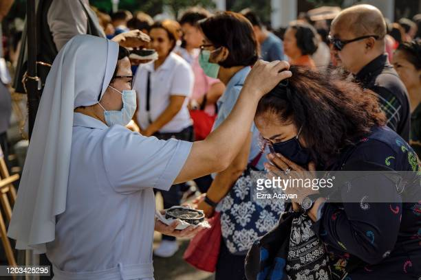 Catholic nun wearing a protective mask sprinkles ash on the head of a devotee during Ash Wednesday services at a church on February 26 2020 in...