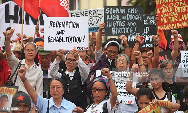 Catholic nuns and activists display placards with antiextrajudicial killings slogan next to the statue of revolutionary hero Andres Bonifacio during...