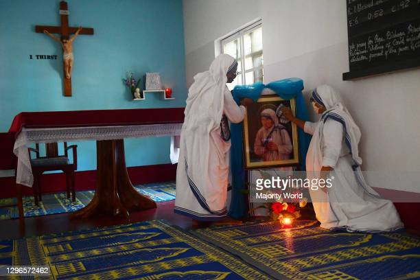 Catholic nuns from Nirmala Shishu Bhavan cleaning the photograph of Mother Teresa, and preparing the place for prayer in remembrance of the 110th...
