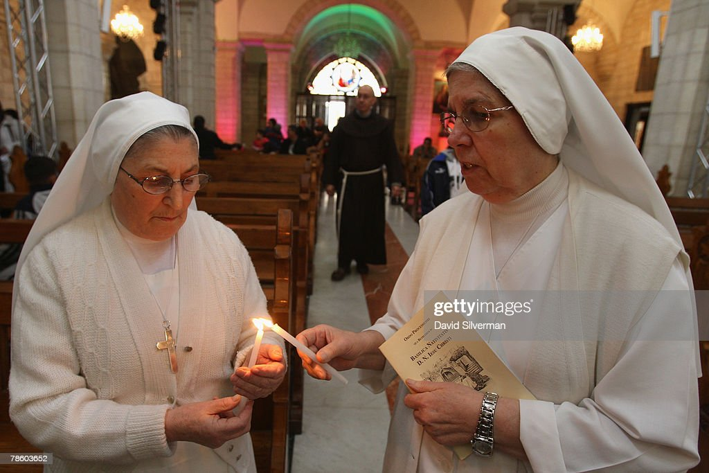 Catholic nuns light candles in St. Catherine's Church before their midday mass in the Grotto of the Church of the Nativity, the traditional birthplace of Jesus, December 21, 2007 in Bethlehem in the West Bank. The biblical town is celebrating both Christmas and the Muslim Eid al-Adha over the next few days.