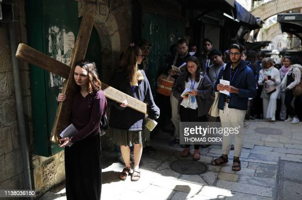 A Catholic pilgrim carries a wooden cross along the Via Dolorosa in Jerusalem's Old City during the Good Friday procession on April 19 2019 Thousands...