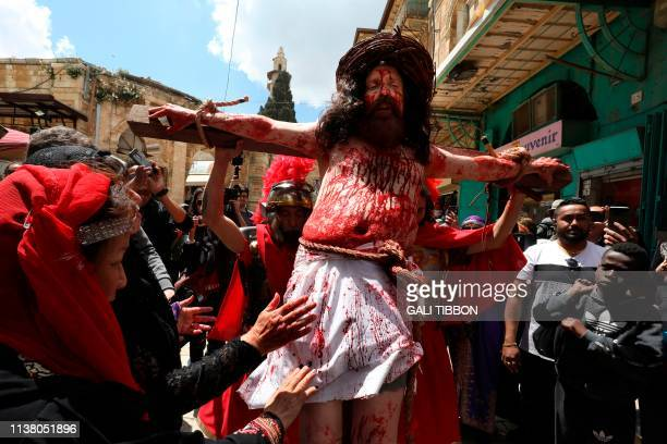 A Catholic pilgrim is tied to a cross along the Via Dolorosa as he reenacts the passion of Jesus Christ in Jerusalem's Old City during the Good...
