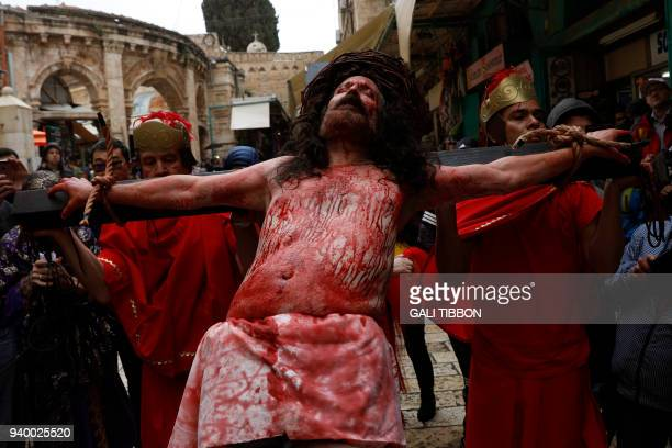 A Catholic pilgrim is tied to a cross as he reenacts the passion of Jesus Christ on the Via Dolorosa in Jerusalem's Old City during the Good Friday...
