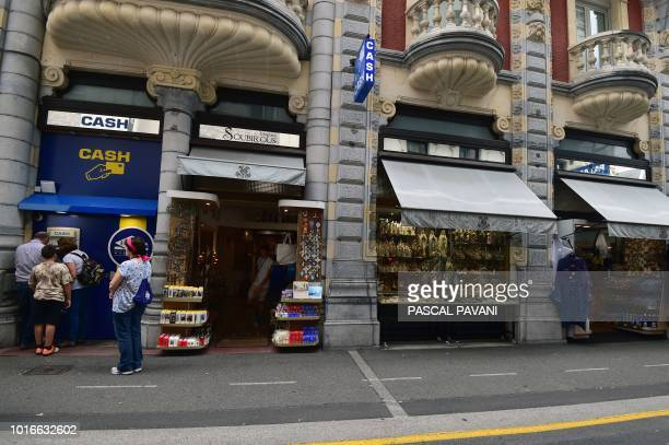 A Catholic pilgrim waits to withdraw money from a cash despenser next door to a shop selling religious articles during the Feast of the Assumption on...