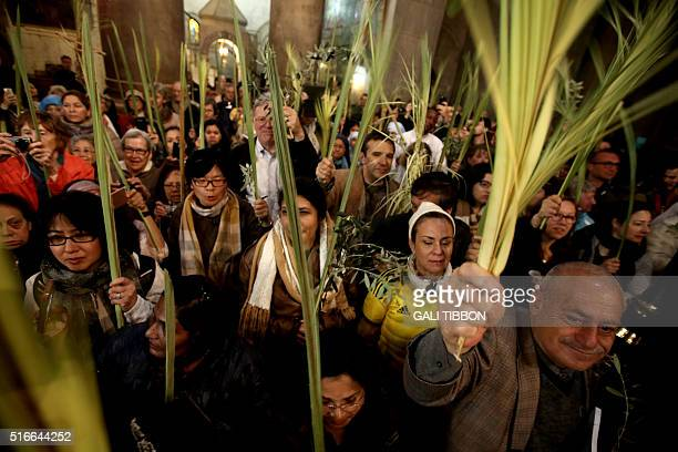 Catholic pilgrims carry palm branches as they circle the aedicule during the Palm Sunday procession at the Church of the Holy Sepulchre in...