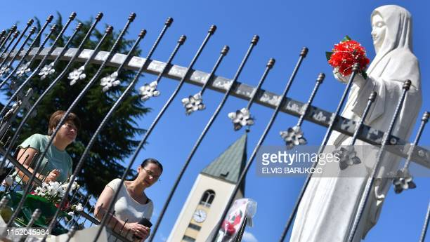 Catholic pilgrims pray in front of a statue of Virgin Marry in front of Franciscan church of St Jacob in SouthernBosnian village of Medjugorje on...
