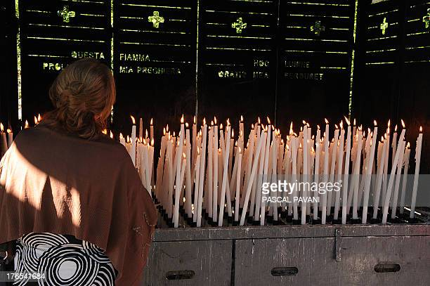 Catholic pilgrims pray in front of lit candles near the Grotto of Massabielle where Bernadette Soubirous said she had a vision during a mass for the...