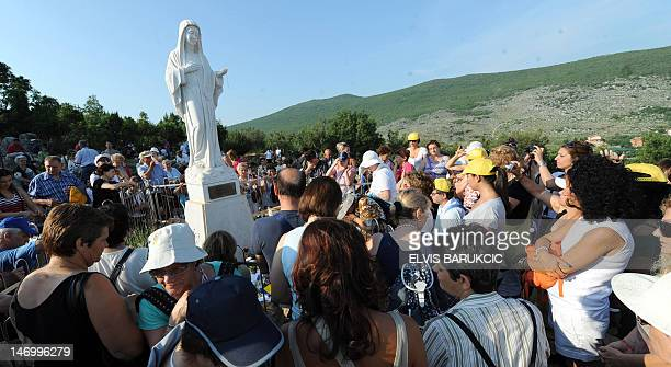 Catholic pilgrims pray on June 25 2012 on their way to a scuplture of Virgin Mary overseeing the area around pilgrimage site near the southern...