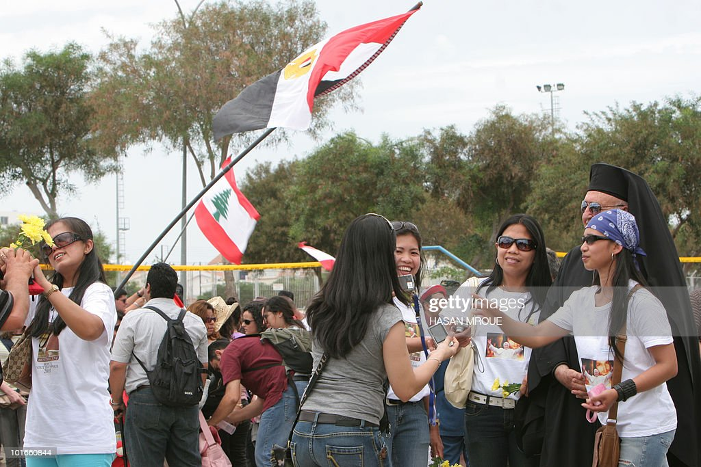 Catholic pilgrims wave Lebanese (L) and Egyptian flags as Filipina believers pose with a Christian cleric from Greece at the end of the pope's mass at Nicosia's Eleftheria Stadium on June 6, 2010, on the third and last day of his visit to Cyprus, a mostly Greek Orthodox Christian Mediterranean island.