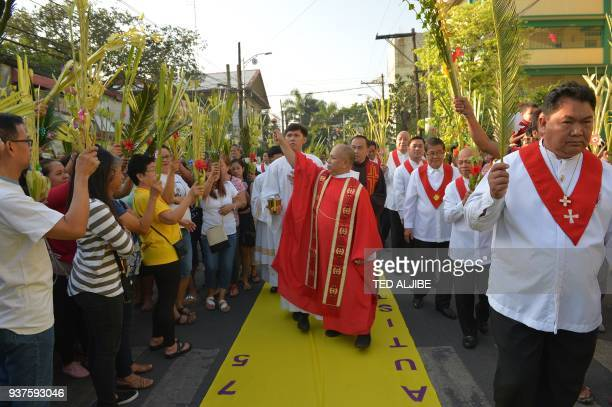 A Catholic priest blesses the faithful holding palms leaves as they walk to the church as part of the traditional lenten devotion in Manila on March...