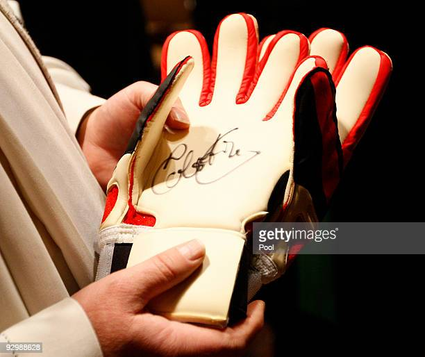 Catholic priest Heinrich Plochg holds the signed goalkeeper gloves of Germany's late national goalkeeper Robert Enke during a mourning service at the...