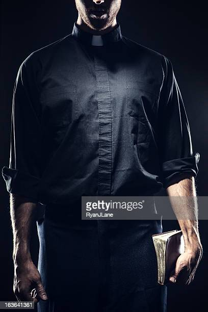 catholic priest holding a bible - katholicisme stockfoto's en -beelden