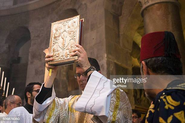 A Catholic priest holds the Book of the Gospels during the celebration of the Holy Thursday mass the Church of the Holy Sepulchre in the Old City of...