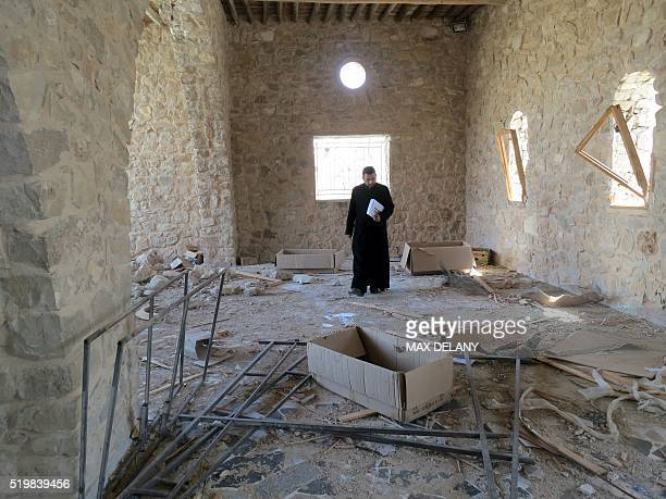 A Catholic priest inspects the damage at Mar Elian monastery on April 8 2016 in alQaryatain a town in the province of Homs in central Syria a few...