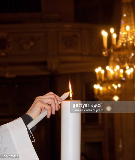 a catholic priest lighting a candle in an italian church during a baptism -  キリスト教 伝来の地  ストックフォトと画像