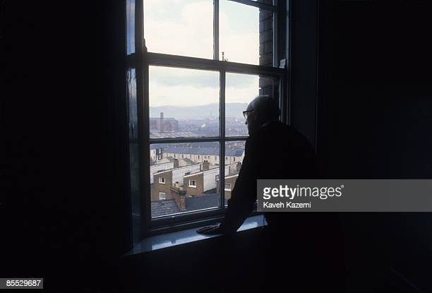 Catholic priest looks out onto the Protestant neighborhoods of west Belfast from a upper floor church window in Falls Road, 18th September 1985.