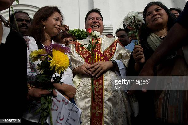 A Catholic priest Michael Chua holds roses as he poses for pictures with Malaysian activists in front of the Church of Our Lady of Lourdes during a...