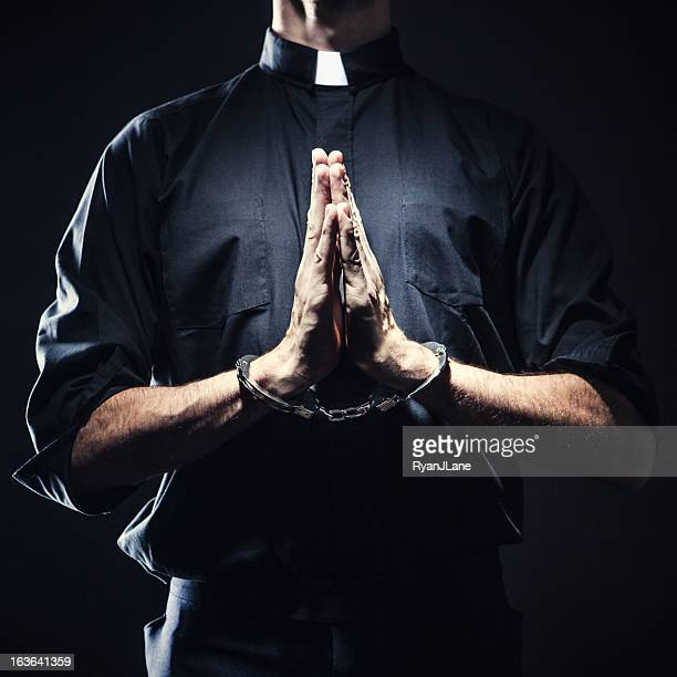 catholic priest praying in handcuffs - vicar stock pictures, royalty-free photos & images