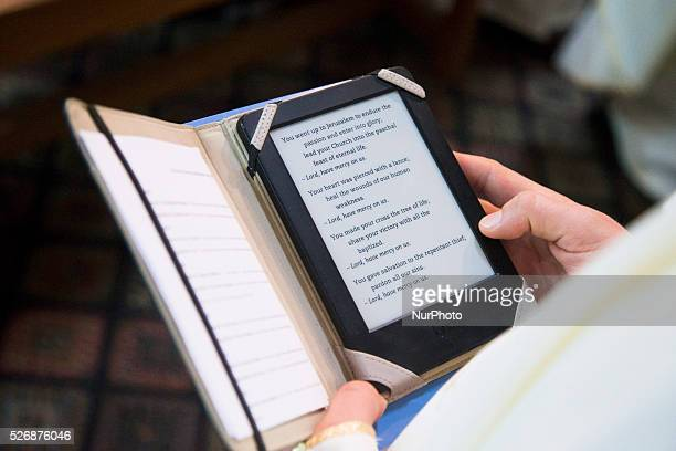 A Catholic priest reads an electornic version of the Book of the Gospels during the celebration of the Holy Thursday mass the Church of the Holy...