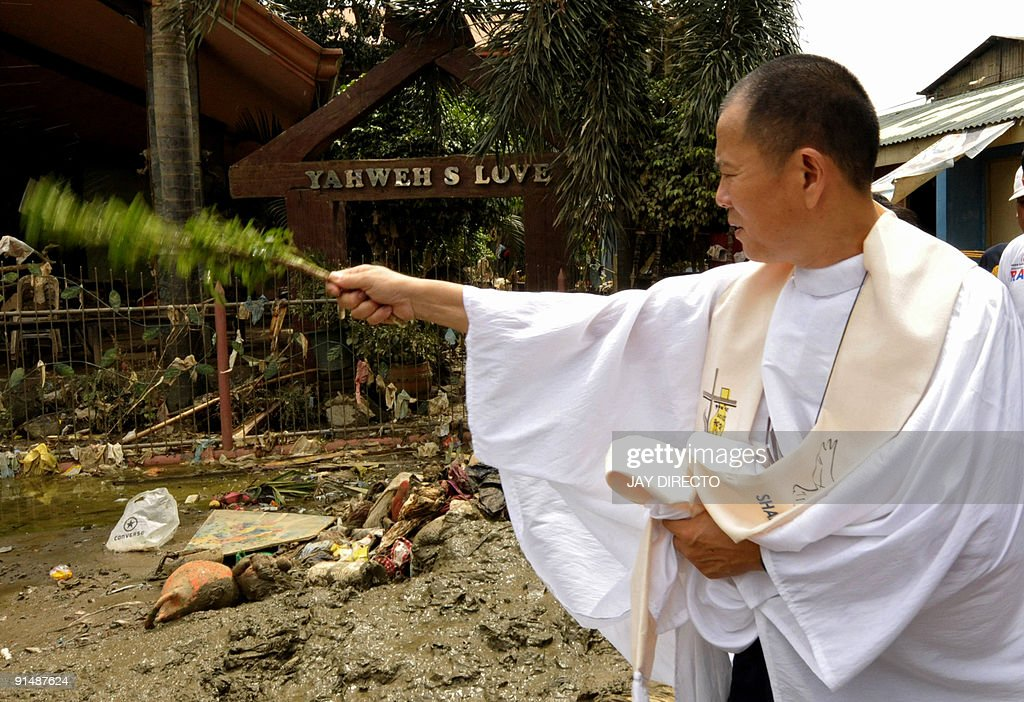 Catholic priest Robert Reyes, wades through mud and uses a