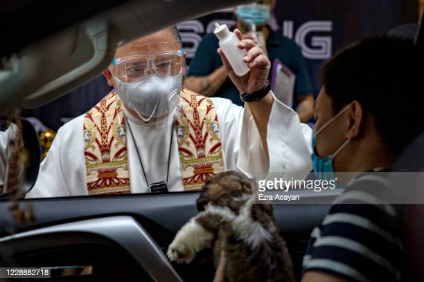 Catholic priest sprinkles holy water on a dog aboard a car via drive-in to prevent the spread of COVID-19, during a pet blessing at Eastwood Mall to...