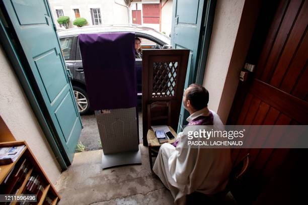 TOPSHOT Catholic priest Vincent Poitau sits at an entrance to the Sainte Jeanne d'Arc church as a parishioner in a vehicle looks out the window to...