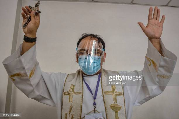 Catholic priest wearing a facemask and face shield blesses a hospital on August 6 2020 in Manila Philippines President Rodrigo Duterte has reimposed...