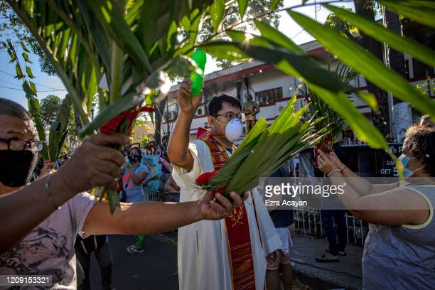 Catholic priest wearing a facemask sprinkles holy water on devotees holding palm fronds as part of Palm Sunday celebrations on April 5 2020 in Quezon...