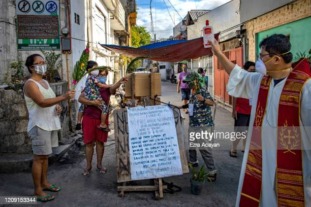 Catholic priest wearing a facemask sprinkles holy water on devotees' palm fronds as part of Palm Sunday celebrations on April 5 2020 in Quezon city...
