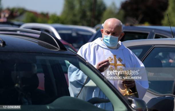 Catholic priest, wearing a protective mask against the spread of the novel coronavirus, COVID-19, serves Holy Communion to some 500 Christian...